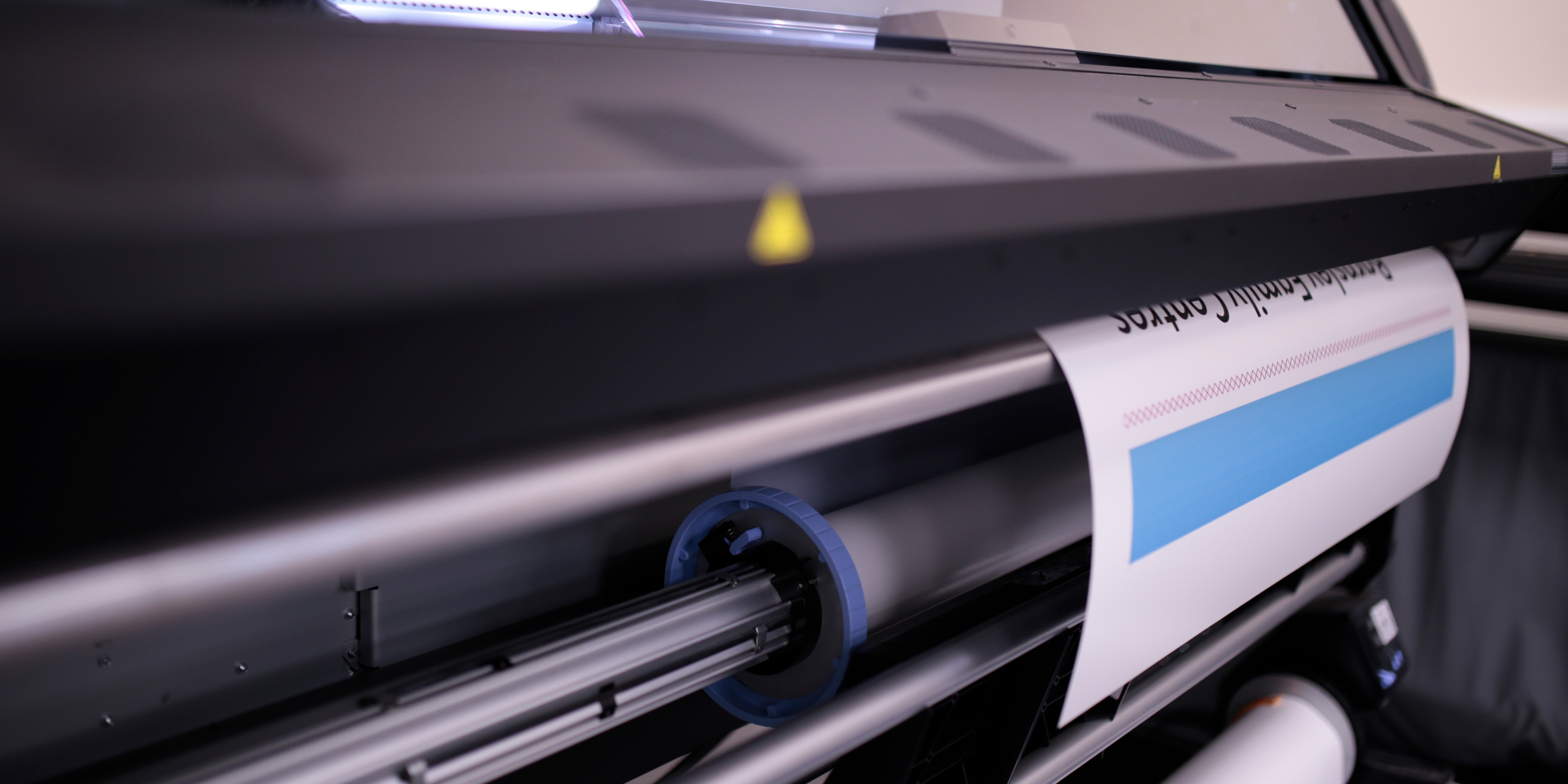 Beginning of a poster being printed on a large format printing machine