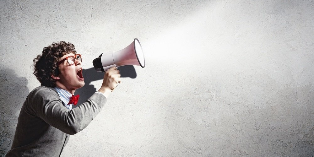 Man shouting into a megaphone to promote an event